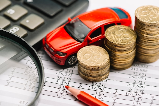 Carro; pilha de moedas; lápis de cor; calculadora e lupa no relatório financeiro Foto gratuita