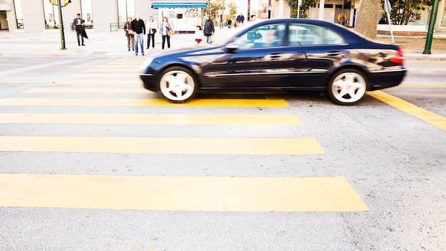 Carro preto dirigindo na estrada com passadeira amarela Foto gratuita