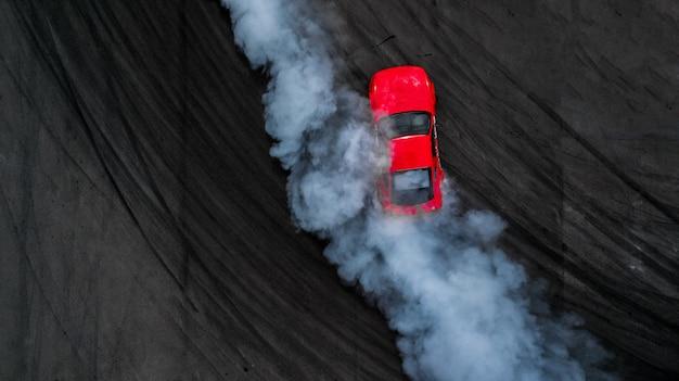 Carro profissional da tração do motorista da vista superior aérea na trilha do asfalto com fumo, vista de cima da tração do carro. Foto Premium