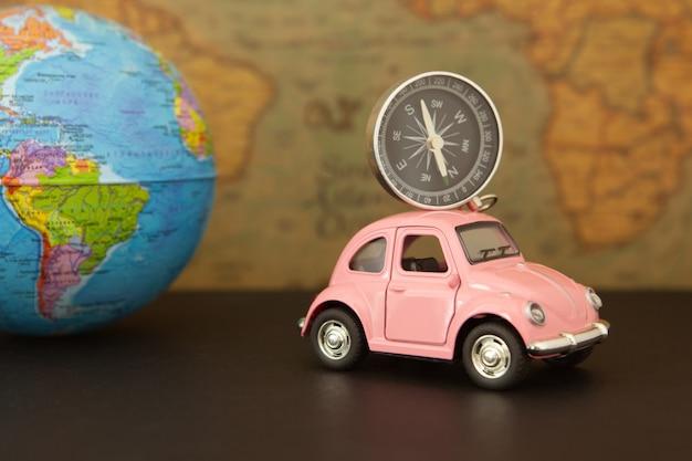Carro retrô rosa com esfera de globo do mundo Foto Premium