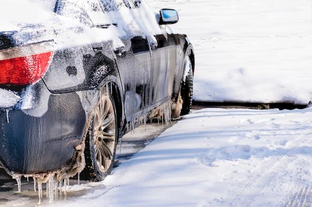 Carro revestido do gelo da chuva de congelação tempo mau da condução na chuva de congelação. Foto Premium