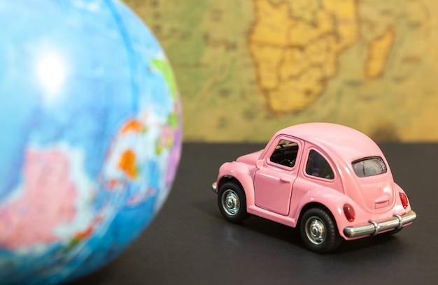 Carro rosa vintage e globo no mapa Foto Premium