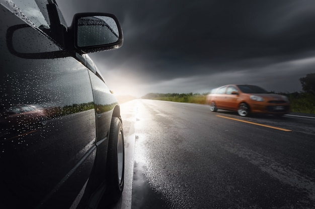 Carro suv compacto preto com nuvens de tempestade, transporte durante condições de mau tempo. Foto Premium