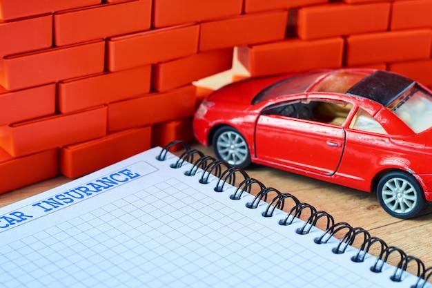 Carro vermelho em miniatura caiu em uma parede de tijolos e formulário de seguro de carro Foto Premium
