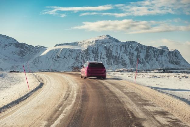 Carro vermelho suv dirigindo na estrada rural com montanha no inverno Foto Premium