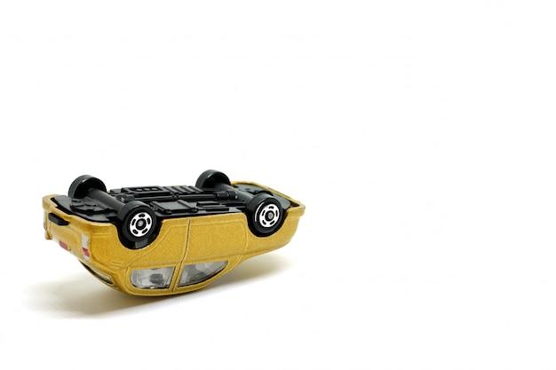 Carros de brinquedo de ouro capotou em um fundo branco, modelo do acidente de carro Foto Premium