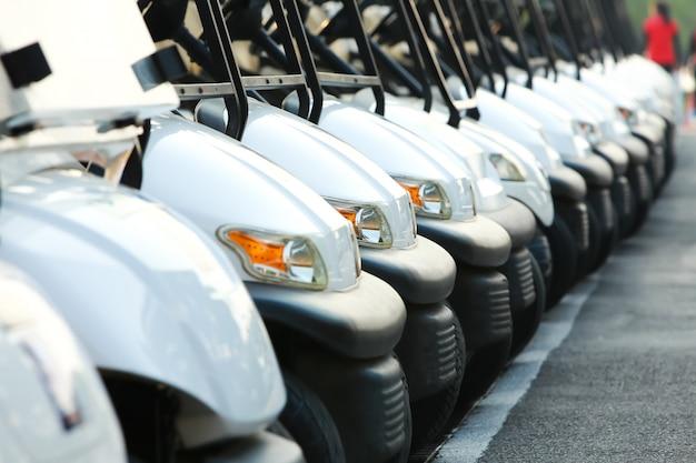 Carros de golfe ou carrinhos de golfe em uma linha ao ar livre em um dia ensolarado de primavera Foto Premium