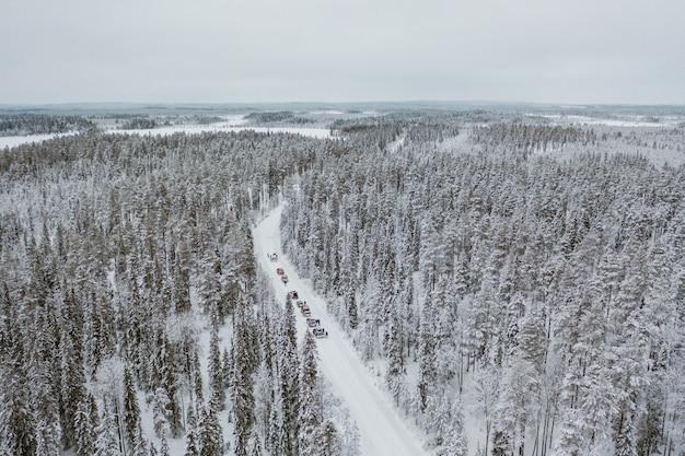 Carros dirigindo por um cenário nevado hipnotizante na finlândia Foto gratuita