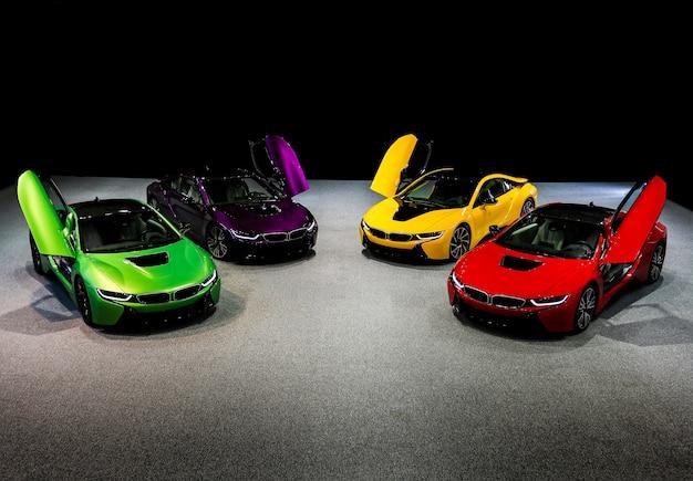 Carros esporte sedan verde, amarelo, vermelho, roxo e violeta em pé no espaço escuro Foto gratuita
