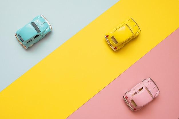 Carros pequenos do brinquedo da cor em um amarelo, em um rosa e em um azul. correndo para a linha de chegada Foto Premium