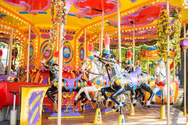 Carrossel francês antigo em um parque de férias. três cavalos em um carrossel tradicional do vintage do recinto de diversão. carrossel com cavalos. Foto Premium