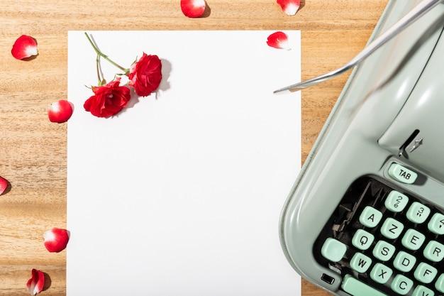 Carta de amor. mesa com papel em branco, máquina de escrever retrô e rosas vermelhas e pétalas Foto Premium