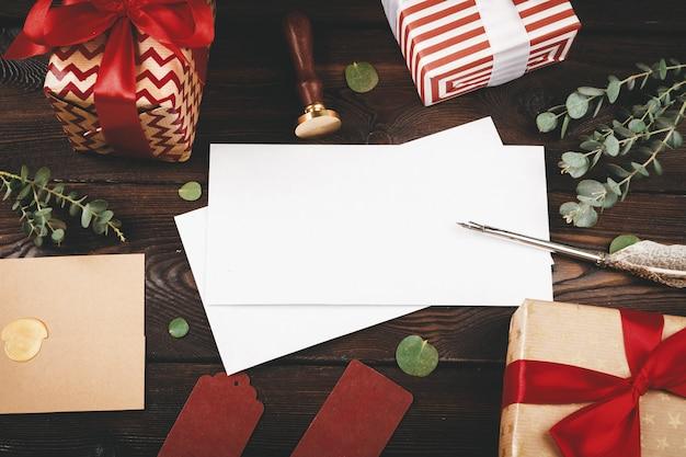 Carta vazia com uma pena no fundo de madeira velha, decorada com objetos de natal Foto Premium