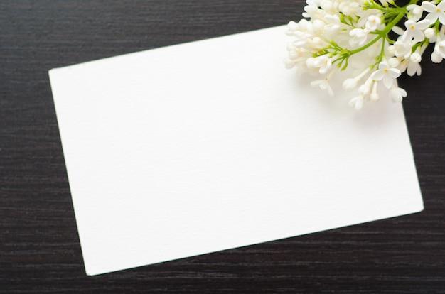 Cartão branco com flor em um fundo preto Foto Premium