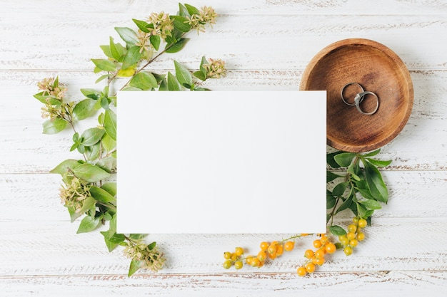 Cartão branco de casamento sobre os anéis; flores e bagas amarelas na mesa de madeira branca Foto gratuita