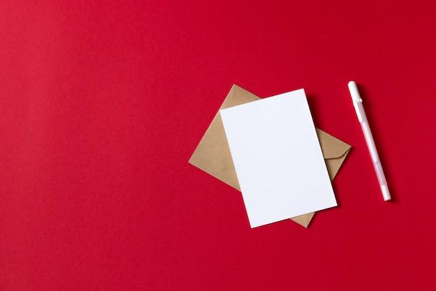 Cartão branco em branco com caneta. folha de papel branco vazio isolada no fundo vermelho Foto Premium