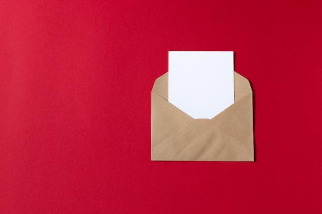 Cartão branco em branco com kraft papel marrom envelope modelo simulado acima Foto Premium