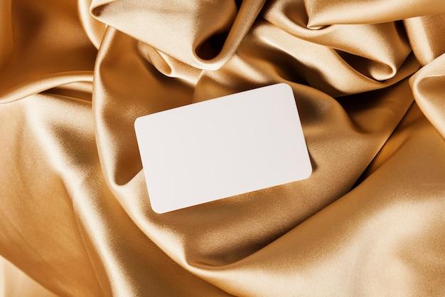 Cartão branco em pano dourado Foto gratuita