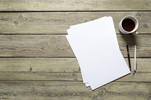 Cartão branco na mesa de madeira. retrato em branco a4. Foto Premium