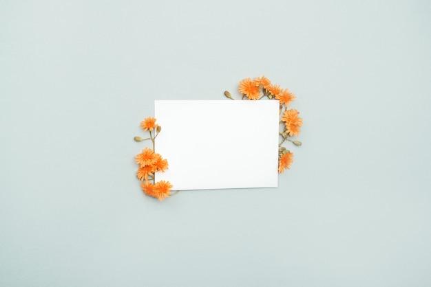 Cartão branco para parabéns e desejos com flores laranja ao redor. Foto Premium