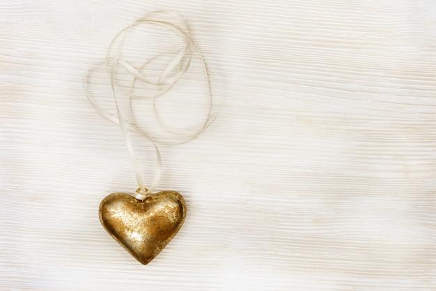 Cartão com coração de ouro com fita e espaço no fundo de madeira velho. vista do topo. Foto Premium