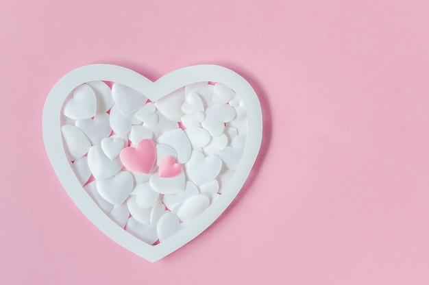 Cartão com corações rosa e brancos e espaço para texto em um fundo rosa. vista do topo. postura plana. dia dos namorados ou conceito de dia das mães. Foto Premium