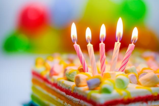 Cartão de aniversário colorido festivo com cinco velas ardentes no bolo arco-íris e balões coloridos no fundo. espaço para texto de felicitações Foto Premium