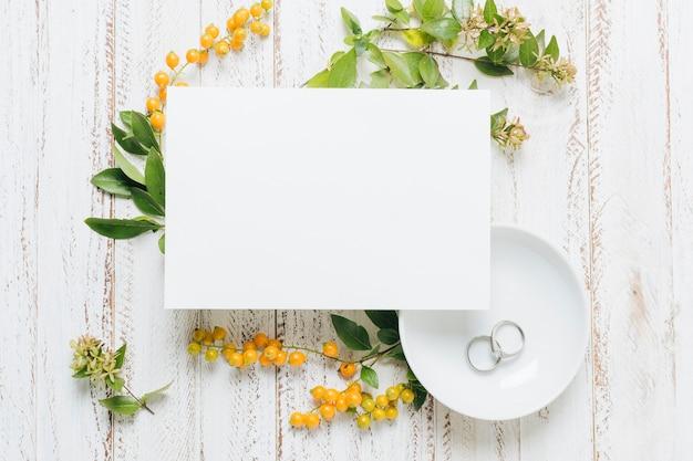 Cartão de casamento branco em branco com flores; bagas amarelas e anéis de casamento no contexto de madeira Foto gratuita