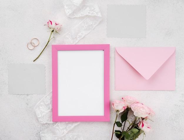 Cartão de convite de casamento com moldura em cima da mesa Foto gratuita