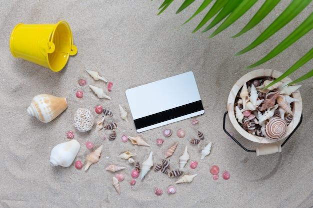 Cartão de crédito e elementos de praia na areia Foto gratuita