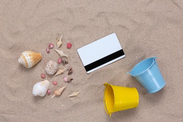 Cartão de crédito e elementos de verão na areia Foto gratuita