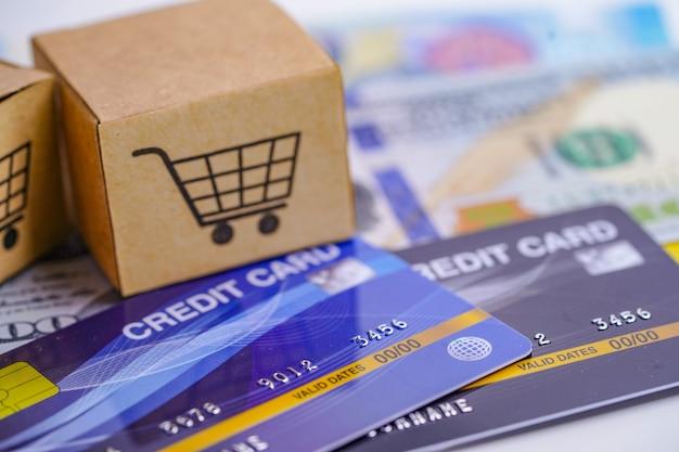 Cartão de crédito e notas de dólar dos eua com caixa de carrinho de compras. Foto Premium