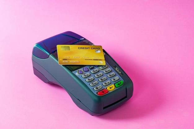 Cartão de crédito e scanner de cartão de crédito em um fundo rosa Foto Premium