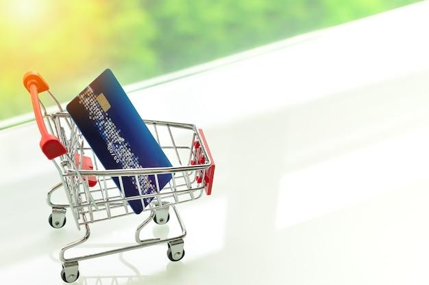 Cartão de crédito no carrinho carrinho de compras na mesa branca com fundos verdes Foto Premium