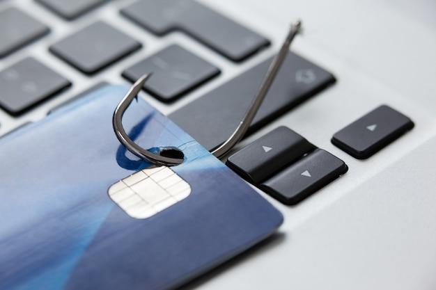 Cartão de crédito no gancho de pesca no laptop Foto Premium