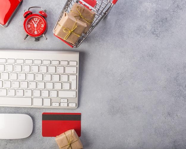 Cartão de crédito vermelho, teclado e presentes de natal na mesa cinza plana leigos, cópia espaço. Foto Premium
