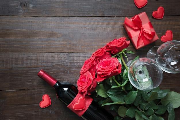 Cartão de dia dos namorados com rosas vermelhas românticas, garrafa de vinho, coração e caixa de presente vermelha na mesa de madeira. vista superior com espaço. Foto Premium