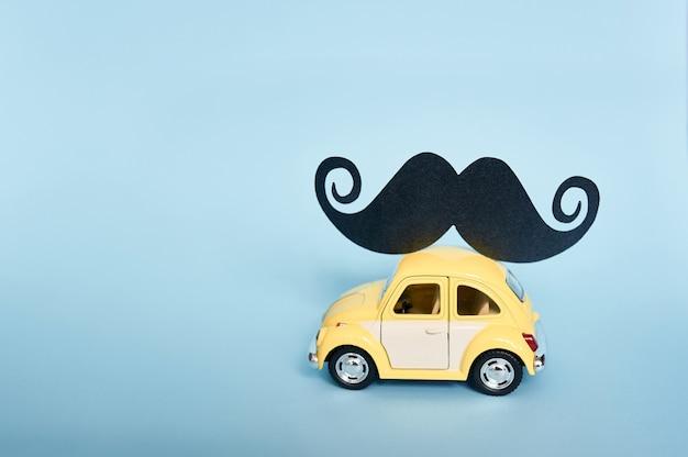 Cartão de dia dos pais com carro de brinquedo amarelo e bigode de papel preto Foto Premium