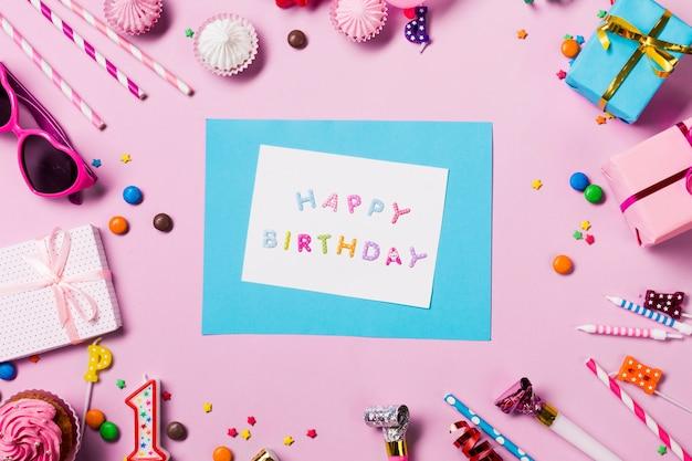 Cartão de feliz aniversário rodeado com itens de aniversário no pano de fundo rosa Foto gratuita