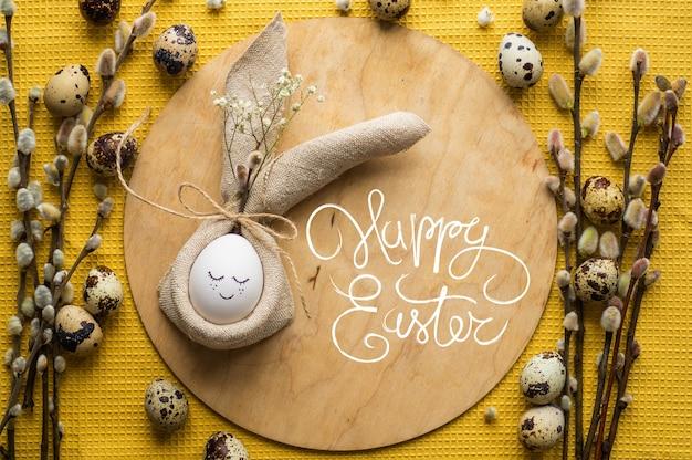 Cartão de feliz páscoa. ovo fofinho num guardanapo em forma de um coelho num prato de cerâmica. ovos de codorniz. galhos de salgueiro. conceito de feliz páscoa Foto Premium