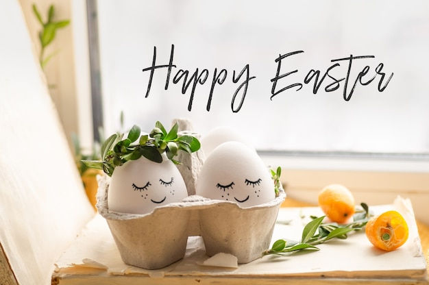 Cartão de feliz páscoa. ovos de páscoa bonitos com uma cara pintada em uma coroa de flores de primavera com espaço de cópia para o texto. feliz páscoa. Foto Premium