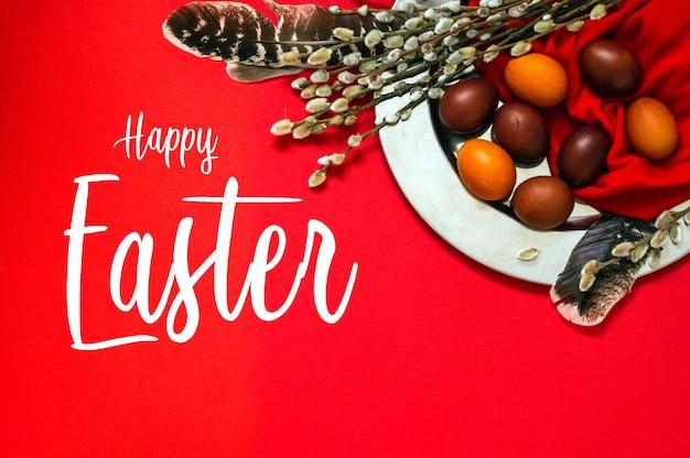 Cartão de feliz páscoa. ovos de páscoa vermelhos bonitos com penas e focas de salgueiro em chapa de ferro. feliz páscoa. Foto Premium