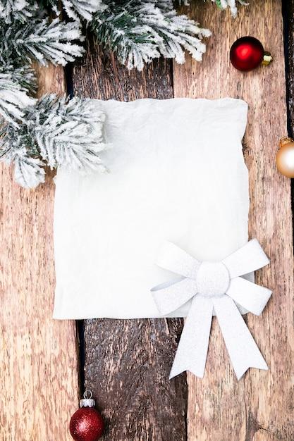 Cartão de natal com bola vermelha e árvore de natal com fundo de madeira Foto Premium