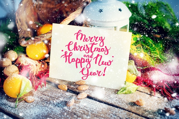 Cartão de natal com mensagem de feliz natal e feliz ano novo. carta, abeto, lanterna, tangerinas, nozes em fundo de madeira. desenho de flocos de neve decorado Foto Premium