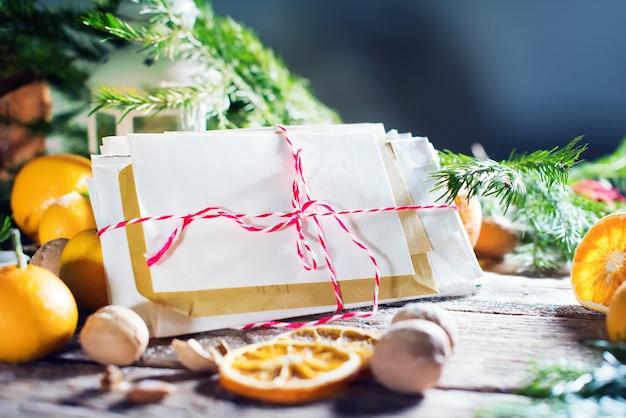 Cartão de natal tema de feliz natal e feliz ano novo. carta, abeto, lanterna, tangerinas, nozes em fundo de madeira. Foto Premium