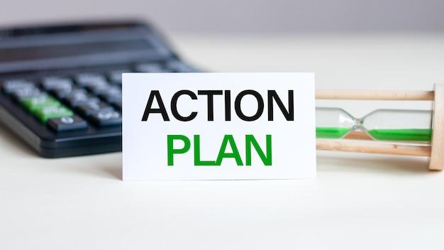 Cartão de papel branco com texto plano de ação folha de papel branco para anotações, calculadora, ampulheta na parede branca. conceito de negócios. Foto Premium