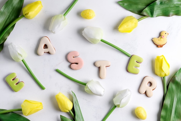 Cartão de páscoa com flores tulipa, ovos de páscoa e biscoito de coelho. vista superior sobre a mesa de mármore branca Foto Premium