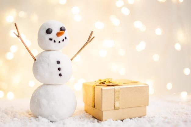 Cartão de presente com um ano novo e natal com uma foto de um boneco de neve com um trenó Foto Premium