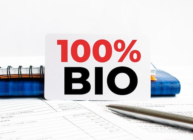 Cartão de visita com texto 100 por cento bio deitado no caderno azul Foto Premium
