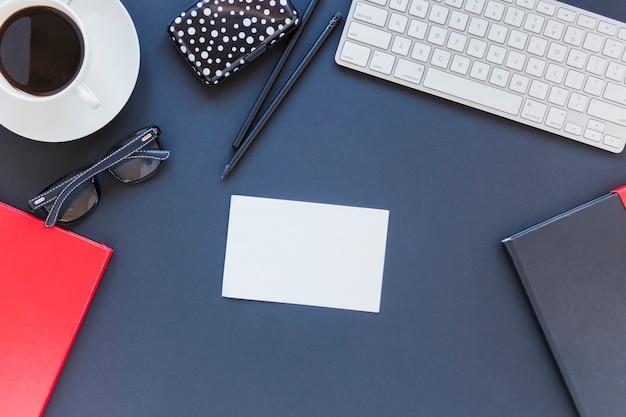 Cartão de visita e artigos de papelaria perto da xícara de café e teclado Foto gratuita